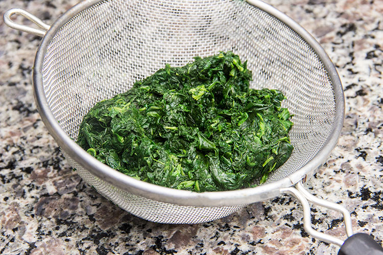 straining-chopped-spinach