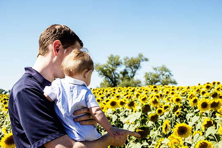 dad-and-baby-in-field-of-sunflowers